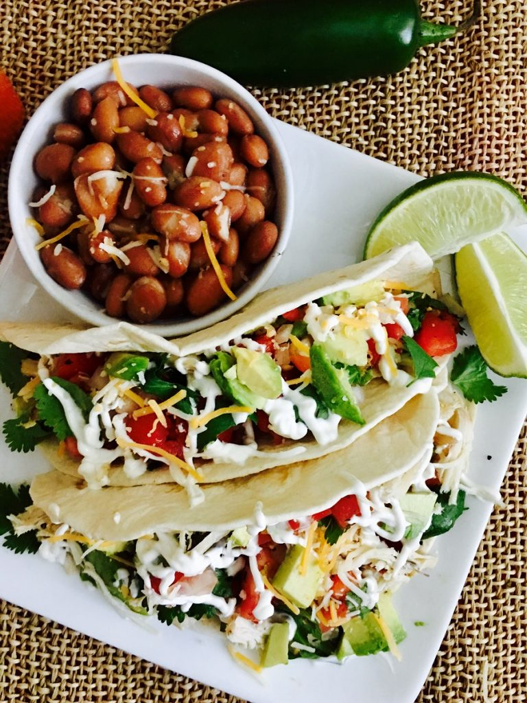 Crockpot Chicken Tacos on a Plate with a Bowl of Beans