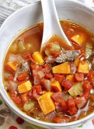 Healthy Instant Pot Vegetable Beef Soup Overhead View of Soup in a White Bowl with a White Spoon