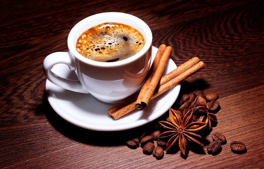 Slow Cooker Holiday Latte Recipes Overhead View of a Cup of Coffee with Raw Cinnamon and Nutmeg