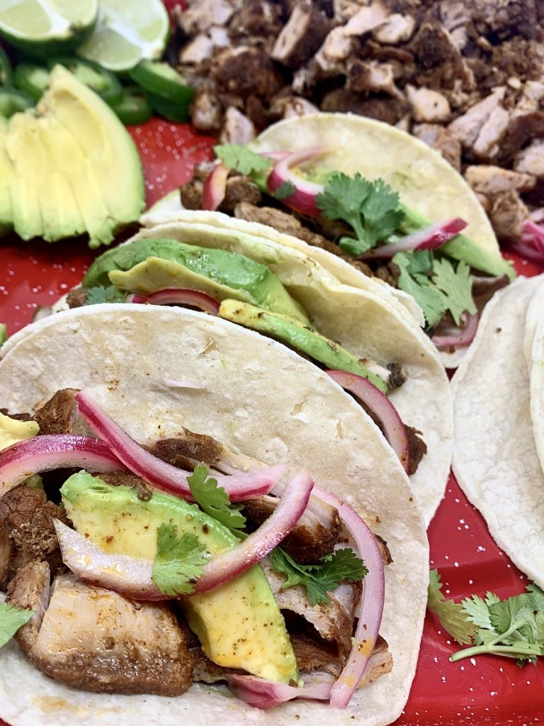 Crockpot Pulled Pork Tacos Recipe Close Up of Tacos on a Red Plate with Sliced Avocado