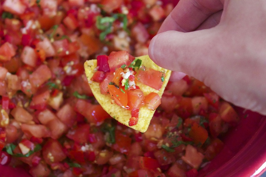 Crockpot Salsa Recipes Person Holding a Chip Above Salsa with Salsa on the Chip