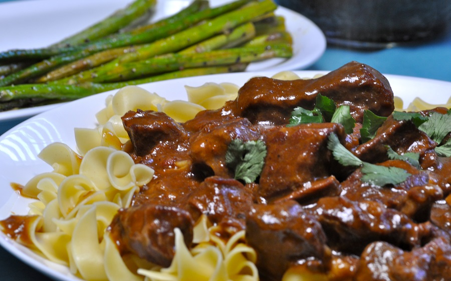 Budget Friendly Beef Stroganoff Close Up of Stroganoff on a Plate with Asparagus in the Background