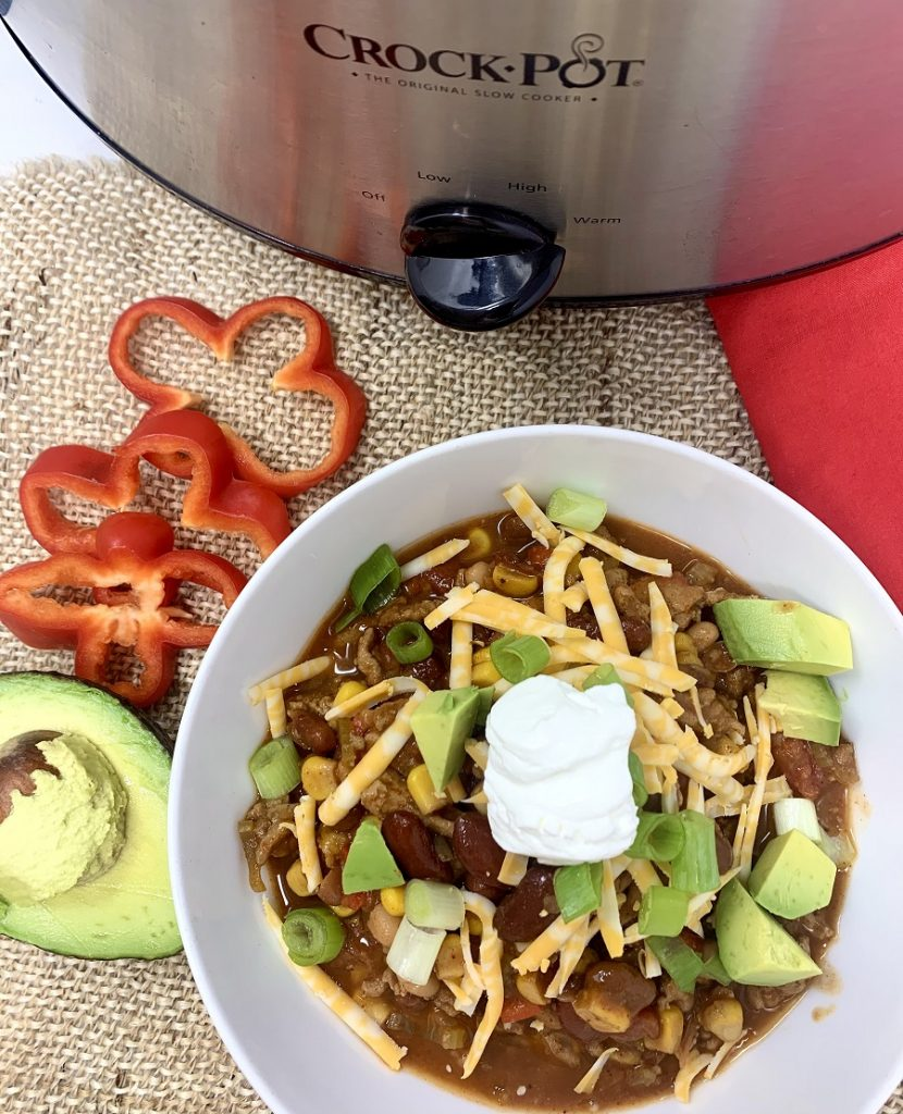 Crockpot Turkey Chili with Pinto Beans Bowl of Chili Next to a Crockpot