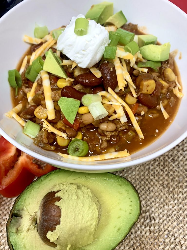 Crockpot Turkey Chili with Pinto Beans a White Bowl Filled with Chili Next to an Avocado Half