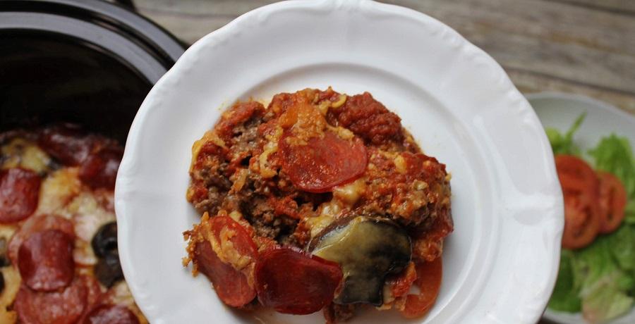 Crockpot Pizza Recipes Casserole on a Plate Held Above a Crockpot