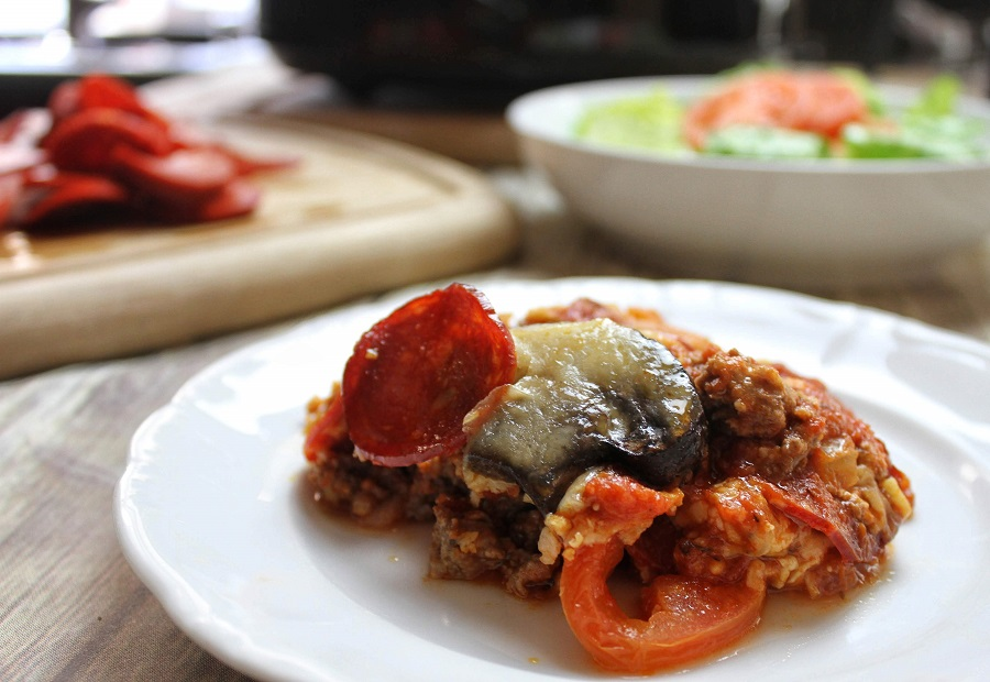 Crockpot Pizza Recipes Casserole on a Plate with a Bowl of Salad in the Background