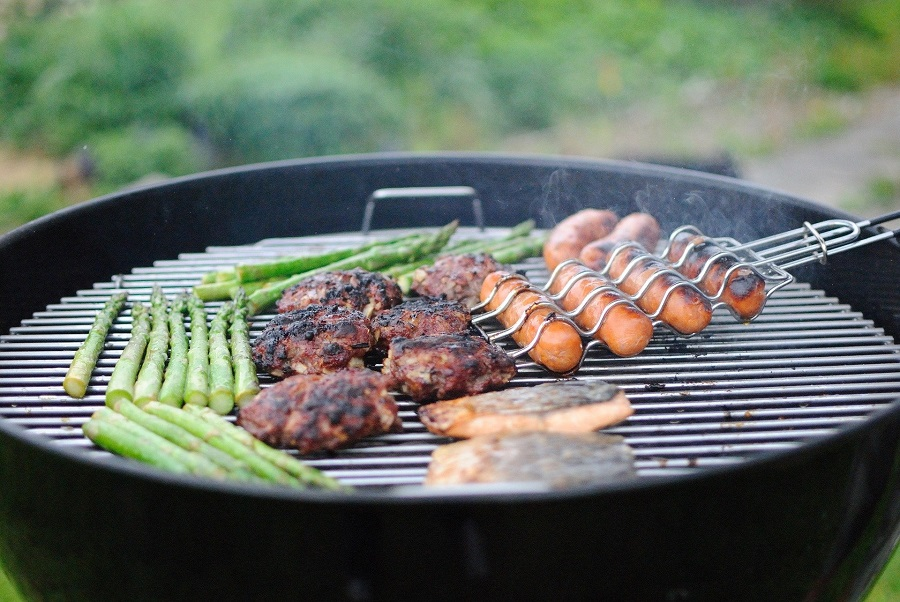Instant Pot Outdoor BBQ Recipes Hot Dogs, Burgers, and Asparagus Grilling on a Round BBQ Pit