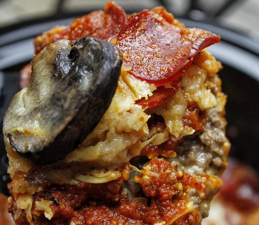 Crockpot Pizza Recipes a Piece of Pizza Casserole On a Fork Held Above a Crockpot