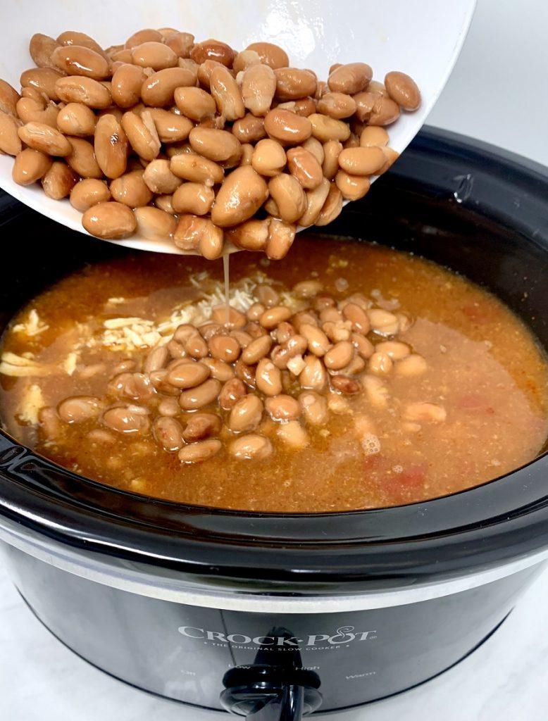 Crockpot Chicken and Rice Burrito Bowl Recipe Person Pouring Beans into Crockpot