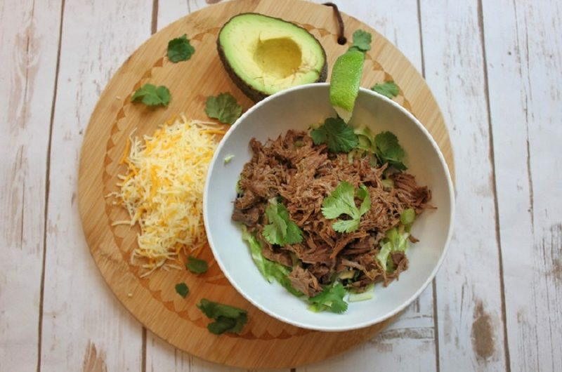 Slow Cooker Beef Barbacoa Recipes Overhead View of Barbacoa Beef in a Bowl with Cheese and a Half an Avocado