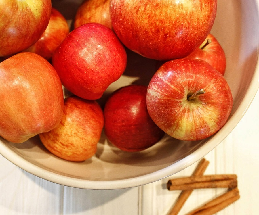 Instant Pot Cinnamon Apples Overhead View of Raw Apples in a Bowl with Cinnamon Sticks Next to it