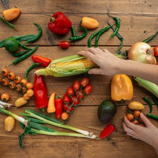 Instant Pot Corn Recipes Assorted Veggies on a Wooden Surface with a Hand Grabbing for the Corn