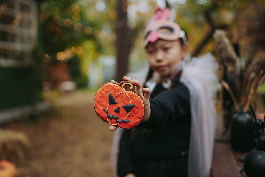 Instant Pot Halloween Recipes Kid in a Costume Holding Up a Jack-O-Lantern Cookie